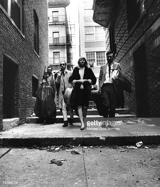 A bass player Paul Stookey Mary Travers and Pater Yarrow of the folk group Peter Paul Mary walk down an alley on July 2 1963