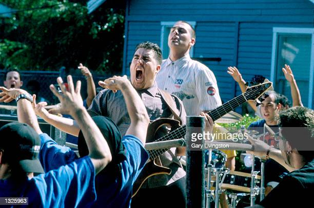 Bass player Tye Zamora of Alien Ant Farm graciously returns the energy the crowd is giving to him while singer Dryden Mitchell looks on during the...