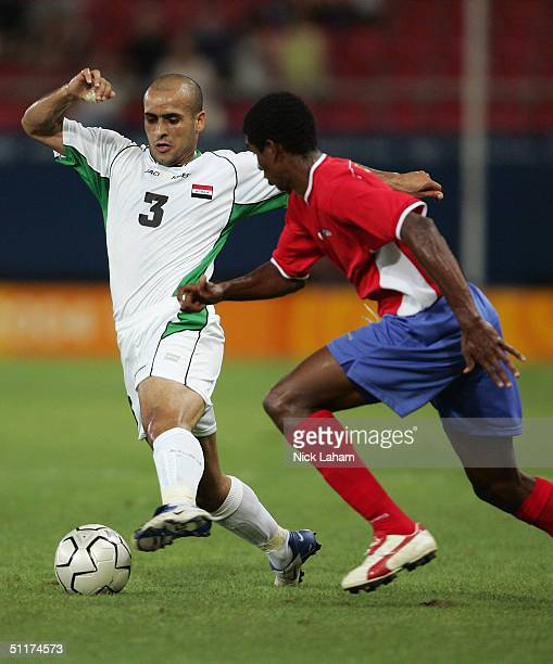 Bassim Abbas of Iraq prepares for the challenge from Roy Myre of Costa Rica chases during the men's football preliminary match on August 15, 2004...