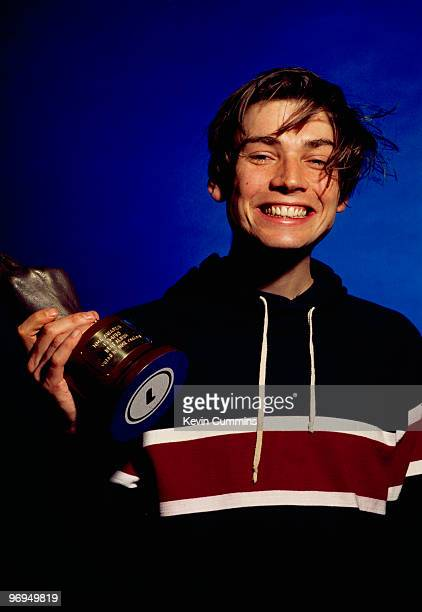 Bassist Alex James of British band Blur holding one of the three awards the band won at the 1995 NME Brat Awards held in London England in February...