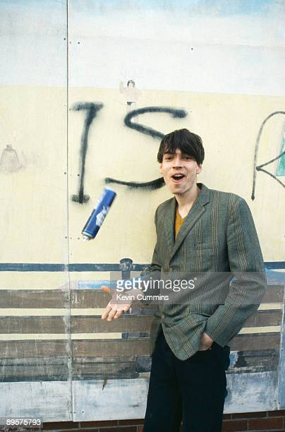 Bassist Alex James of English alternative rock band Blur poses in front of the graffiti slogan 'Modern Life is Rubbish' the title of Blur's 1993 album