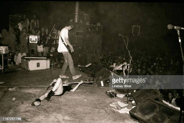 Bassist and vocalist Kim Gordon continues to play bass while on her back on stage with guitarist and vocalist Thurston Moore guitarist Lee Renaldo...