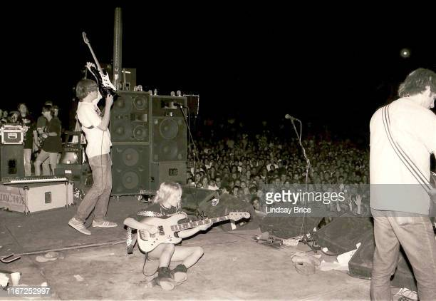 Bassist and vocalist Kim Gordon plays bass while seated on the stage performing with guitarist and vocalist Thurston Moore lifting his guitar high...