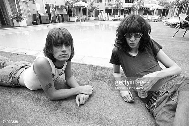 Bassist Dee Dee Ramone and singer Joey Ramone of the punk band 'The Ramones' lounge poolside as Joey drinks a can of Michelob beer at a hotel in...