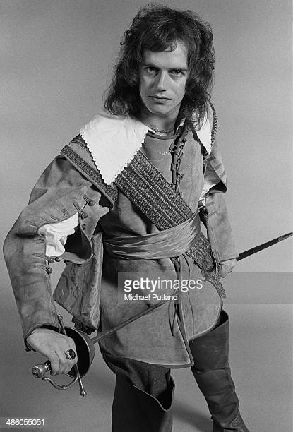 Bassist Jim Lea of English rock group Slade posing in a cavalier costume and holding a sword London 1974