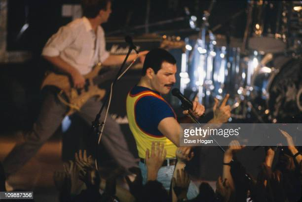 Bassist John Deacon and singer Freddie Mercury performing on stage with British rock group Queen, 1986.