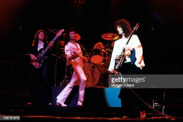 Bassist John Deacon singer Freddie Mercury drummer Roger Taylor and guitarist Brian May of British rock band Queen performing on stage in 1974