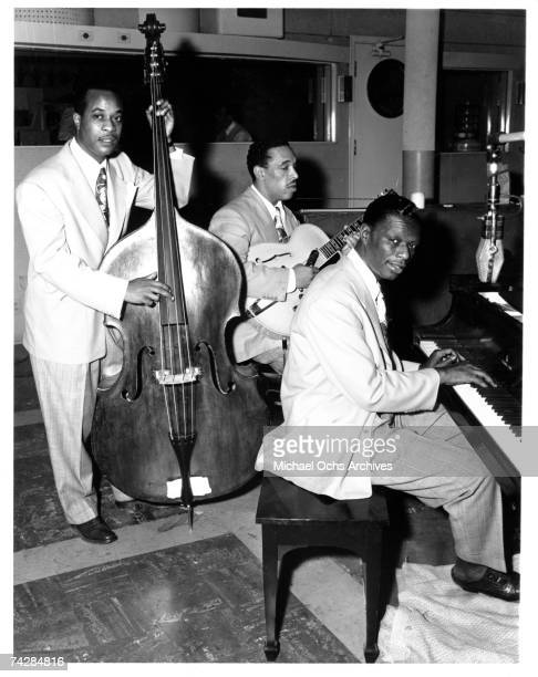 Bassist Johnny Miller guitarist Oscar Moore and pianist Nat 'King' Cole of the Nat 'King' Cole Trio record in Capitol Records studios on March 15...