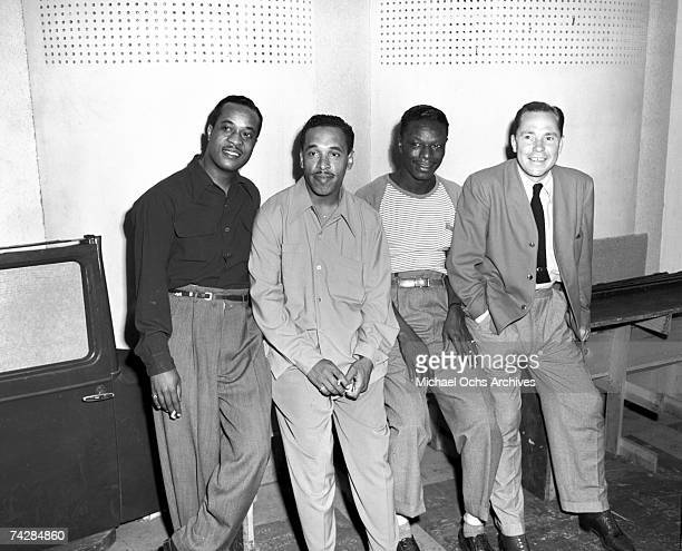 Bassist Johnny Miller guitarist Oscar Moore and pianist Nat 'King' Cole of the 'Nat 'King' Cole Trio' pose for a portrait with Johnny Mercer in...