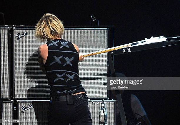 Bassist Mike Dirnt of Green Day smashes his bass as he performs onstage during the 2012 iHeartRadio Music Festival at the MGM Grand Garden Arena on...