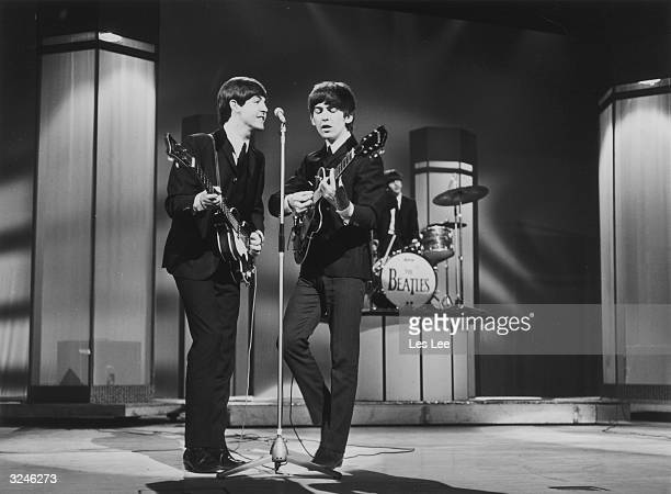 Bassist Paul McCartney and guitarist George Harrison sing at a microphone as the Beatles perform at the London Palladium Drummer Ringo Starr plays...