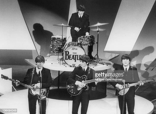 Bassist Paul McCartney, guitarists George Harrison and John Lennon and Drummer Ringo Starr of the rock and roll band 'The Beatles' perform during...