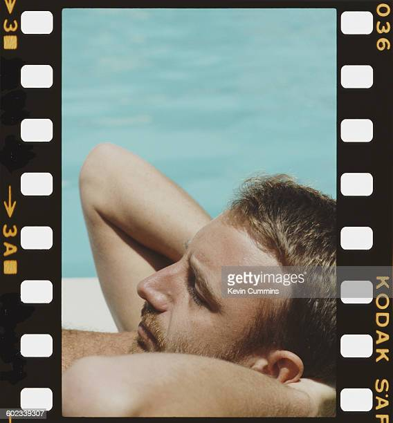 Bassist Peter Hook of English rock group New Order relaxing by a swimming pool Washington DC 9th July 1983
