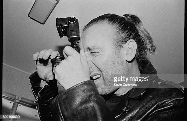 Bassist Peter Hook of English rock group New Order taking a photograph backstage at the Reading Festival 25th August 1989