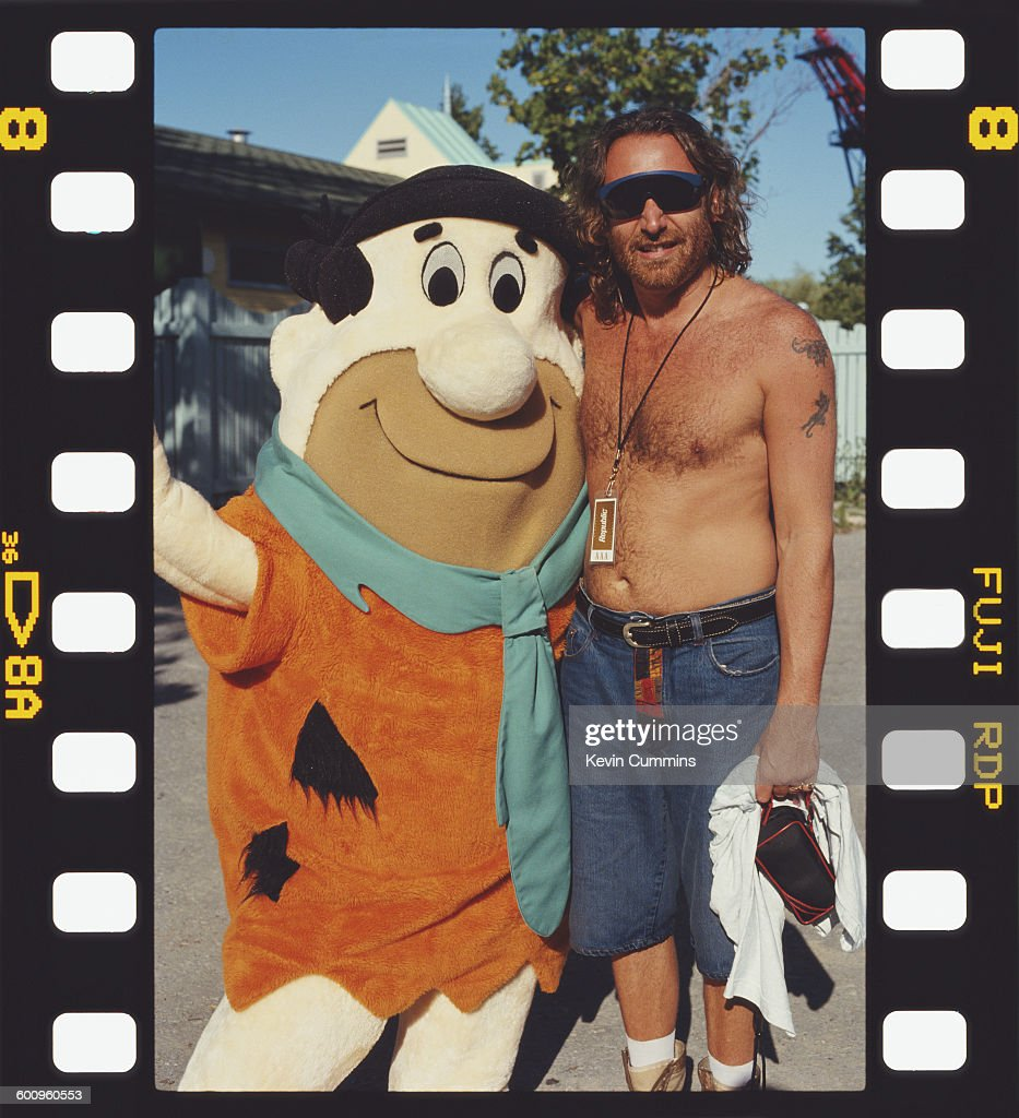 Bassist Peter Hook of English rock group New Order (right) with a person in a Fred Flintstone costume, at the Canada's Wonderland theme park in Vaughan, Ontario, before a show at the Kingswood Music Theatre, 31st July 1993.