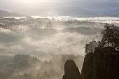 Bastei area with Mönch (Mönchstein) rock pinnacle in early morning fog, Saxon Switzerland National Park, Saxony, Germany, Europe