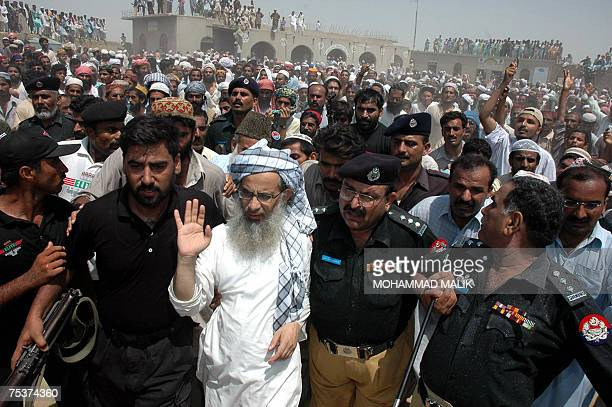 Pakistani policemen escort Abdul Aziz chief cleric of The Red Mosque as he arrives in the village of Basti Abdullah 12 July 2007to attand the last...