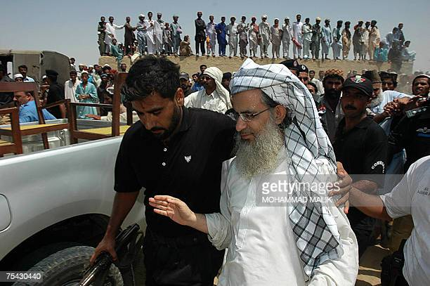 Pakistani policemen escort Abdul Aziz chief cleric of The Red Mosque as he arrives in the village of Basti Abdullah 12 July 2007to attend the last...
