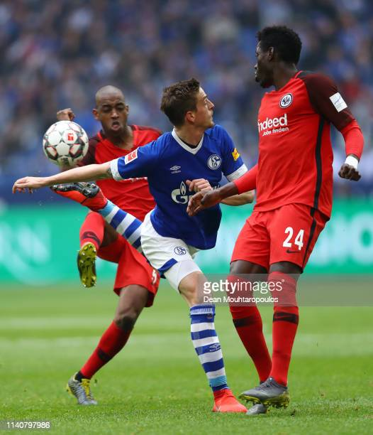 Bastian Oczipka of FC halke 04 controls the ball as he is challenged by Danny Da Costa of Eintracht Frankfurt and Gelson Fernandes of Eintracht...