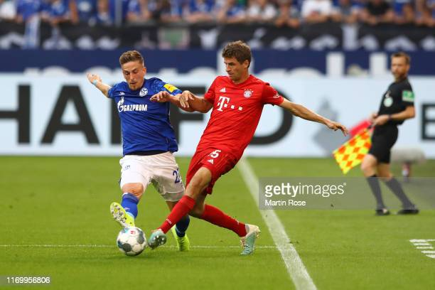 Bastian Oczipka of FC Schalke 04 battles for possession with Thomas Muller of FC Bayern Munich during the Bundesliga match between FC Schalke 04 and...