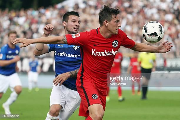 Bastian Oczipka of Frankfurt is challenged by Jerome Gondorf of Darmstadt during the Bundesliga match between SV Darmstadt 98 and Eintracht Frankfurt...