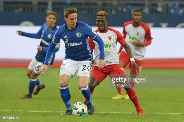 Bastian Oczipka of Schalke and Daniel Opare of Augsburg battle for the ball during the Bundesliga match between FC Schalke 04 and FC Augsburg at...