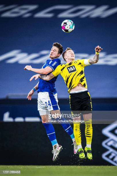 Bastian Oczipka of Schalke and Marco Reus of Dortmund in action during the Bundesliga match between FC Schalke 04 and Borussia Dortmund at...