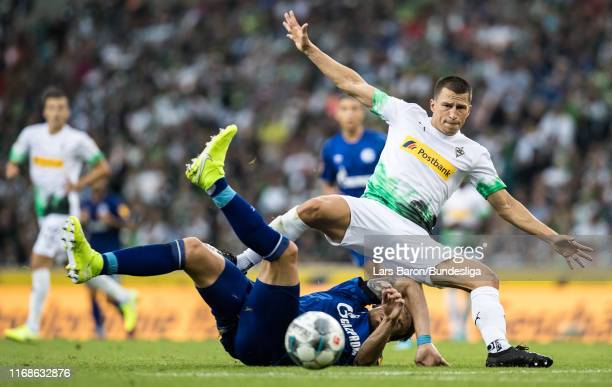 Bastian Oczipka of Schalke challenges Stefan Lainer of Mönchengladbach during the Bundesliga match between Borussia Mönchengladbach and FC Schalke 04...
