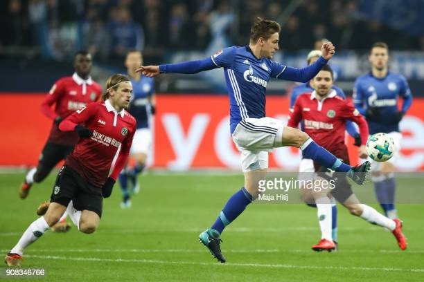 Bastian Oczipka of Schalke controls the ball next to Iver Fossum of Hannover 96 and Julian Korb of Hannover 96 during the Bundesliga match between FC...
