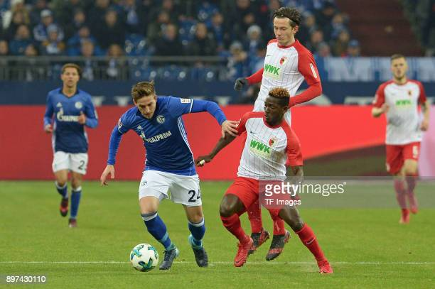 Bastian Oczipka of Schalke Daniel Opare of Augsburg and Michael Gregoritsch of Augsburg battle for the ball during the Bundesliga match between FC...