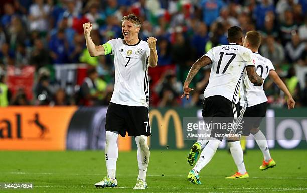 Bastian Schweinsteiger and Germany players celebrate their win through the penalty shootout after Jonas Hector scores to win the game after the UEFA...