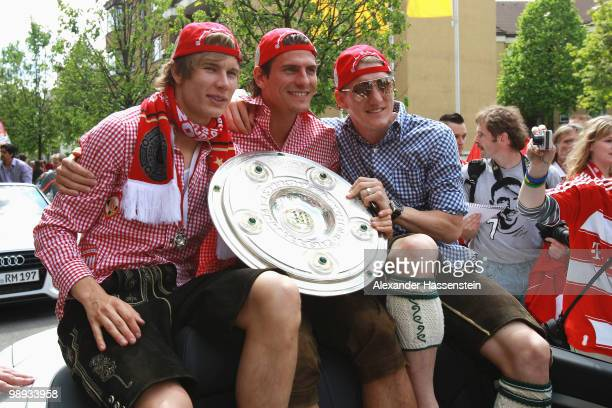 Bastian Schweinsteiger and his team mates Mario Gomez as well as Holger Badstuber celebrate the German championship with the trophy on the way to the...