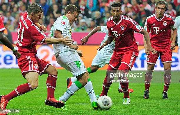 Bastian Schweinsteiger and Jerome Boateng of Muenchen challenge Max Kruse of Moenchengladbach during the Bundesliga match between FC Bayern Muenchen...