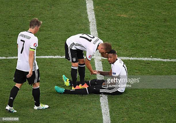 Bastian Schweinsteiger and Joshua Kimmich of Germany talk to injured Jerome Boateng during the UEFA EURO semi final match between Germany and France...