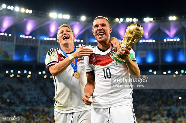 Bastian Schweinsteiger and Lukas Podolski of Germany celebrate with the World Cup trophy after the 2014 FIFA World Cup Brazil Final match between...