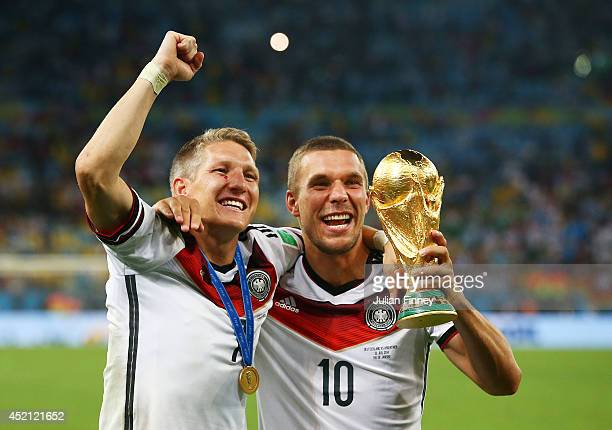 Bastian Schweinsteiger and Lukas Podolski of Germany celebrate with the World Cup trophy after defeating Argentina 1-0 in extra time during the 2014...