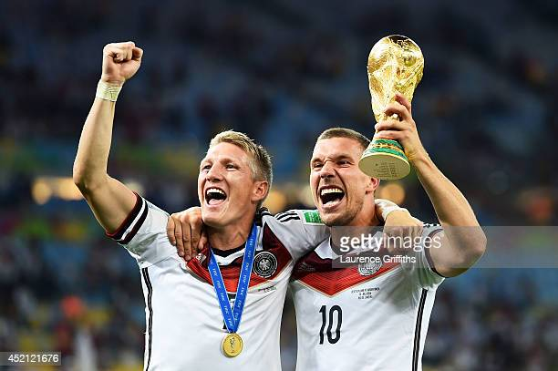 Bastian Schweinsteiger and Lukas Podolski of Germany celebrate with the World Cup trophy after defeating Argentina 10 in extra time during the 2014...