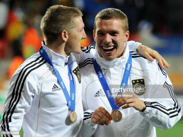 Bastian Schweinsteiger and Lukas Podolski of Germany celebrates with the bronze medal after the 2010 FIFA World Cup third place match between Uruguay...