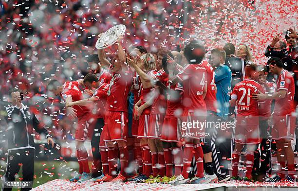 Bastian Schweinsteiger celebrates with FC Bayern Muenchen team mates as they receive the championship trophy after the Bundesliga match between FC...