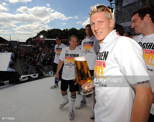 Bastian Schweinsteiger holds a beer in front of members of the German national football team while celebrating at the Fan Mile in front of the...