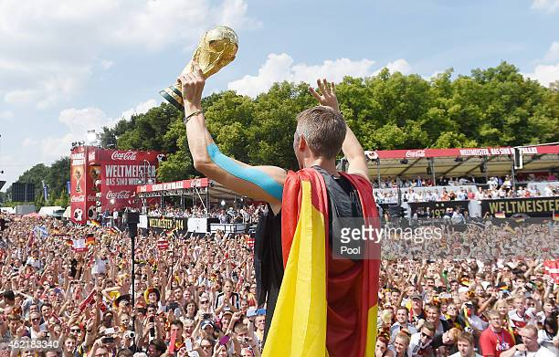 Bastian Schweinsteiger holds up the trophy to fans as they celebrate during the German team victory ceremony on July 15 2014 in Berlin Germany...