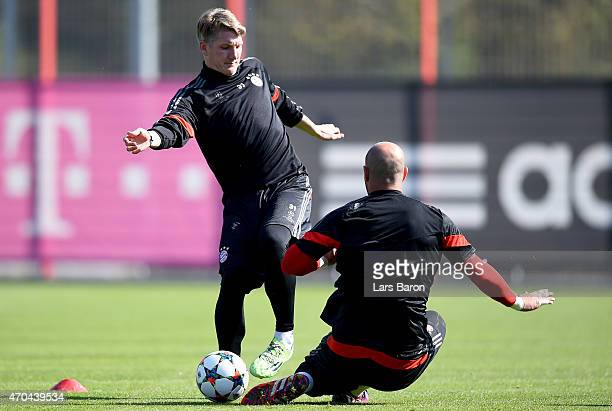 Bastian Schweinsteiger is challenged by Pepe Reina during a FC Bayern Muenchen training session prior to their UEFA Champions League Quarter Final...