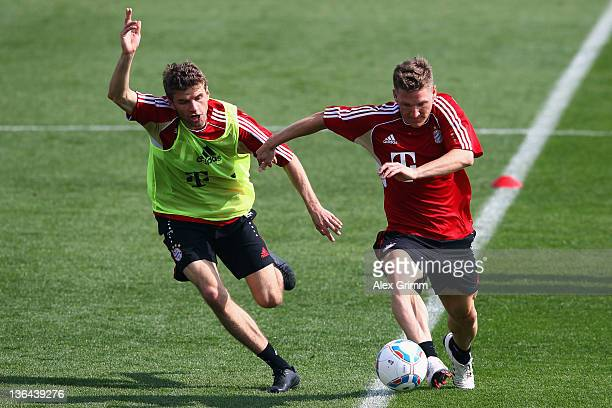 Bastian Schweinsteiger is challenged by Thomas Mueller during a training session of Bayern Muenchen at the ASPIRE Academy for Sports Excellence on...