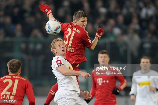 Bastian Schweinsteiger of Bayern and Mike Hanke of Moenchengladbach jump for a header during the Bundesliga match between Borussia Moenchengladbach...