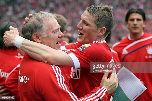Bastian Schweinsteiger of Bayern embraces assistant coach Hermann Gerland after winning ther German champions trophy after winning 31 the Bundesliga...
