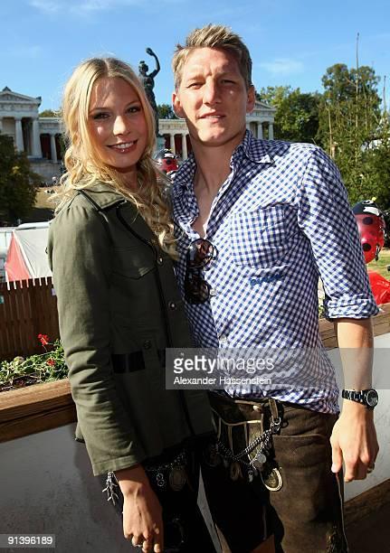 Bastian Schweinsteiger of Bayern Muenchen and girlfriend Sarah Brandner attend the Oktoberfest beer festival at the Kaefer Wiesnschaenke tent on...