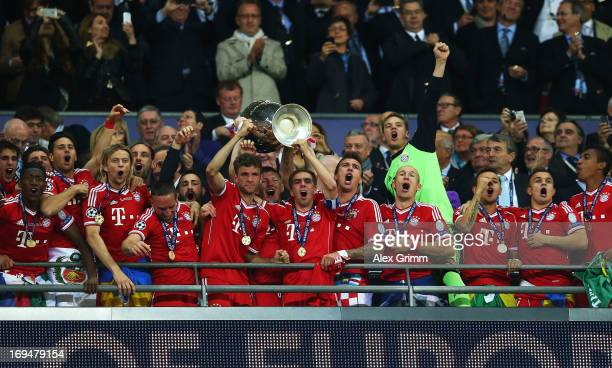 Bastian Schweinsteiger of Bayern Muenchen and teammate Philipp Lahm lift the trophy after winning the UEFA Champions League final match against...