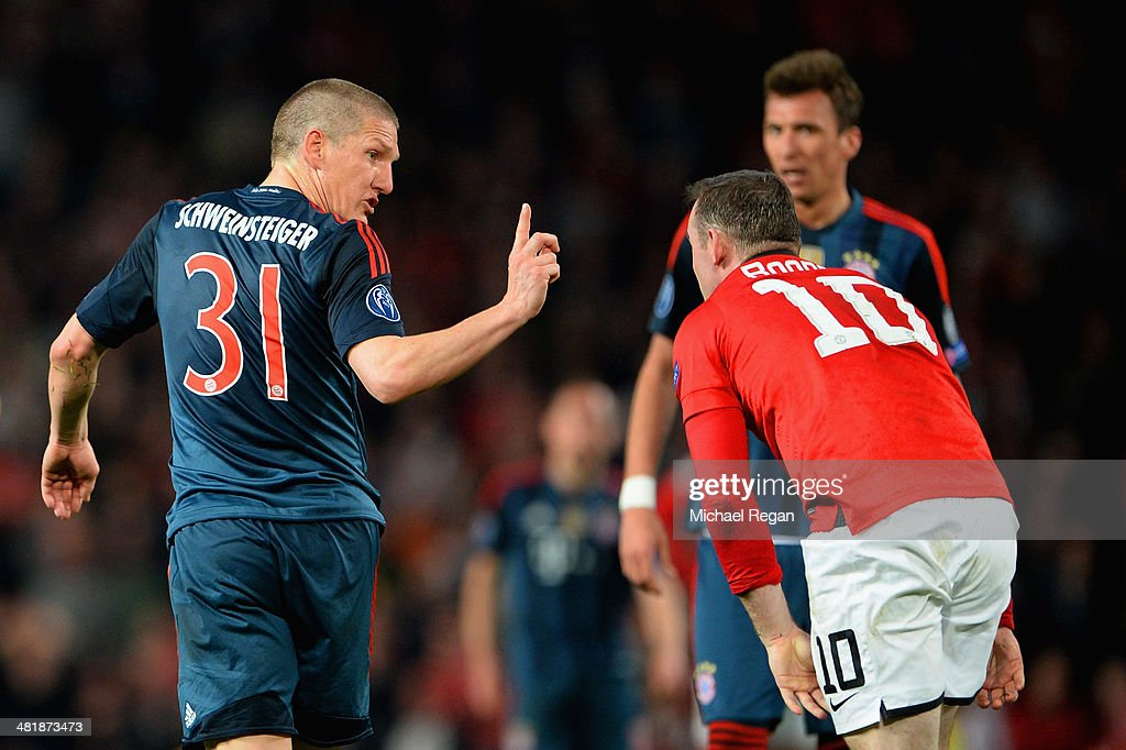 Bastian Schweinsteiger of Bayern Muenchen argues with Wayne Rooney of Manchester United after he received a red card during the UEFA Champions League Quarter Final first leg match between Manchester United and FC Bayern Muenchen at Old Trafford on April 1, 2014 in Manchester, England.