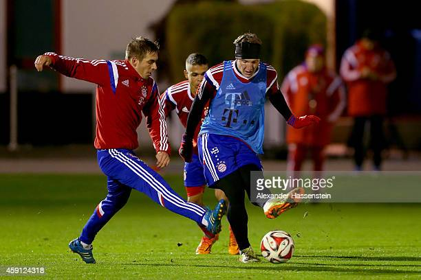 Bastian Schweinsteiger of Bayern Muenchen battels for the ball with his team mate Philipp Lahm during a training session at Bayern Muenchen's...