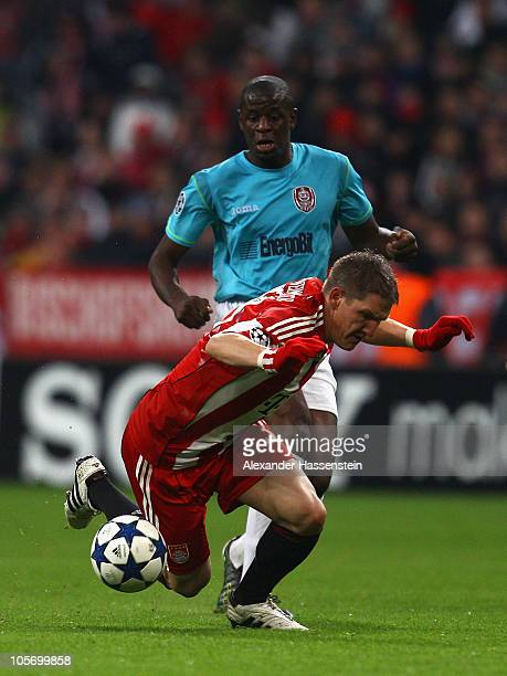 Bastian Schweinsteiger of Bayern Muenchen battles for the ball with Dominique Kivuvu of Cluj during the UEFA Champions League group E match between...